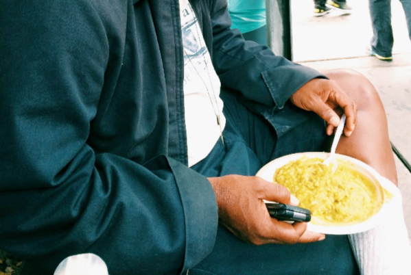 A homeless man holds his meal and a flip phone in the garden of the Hospitality Kitchen